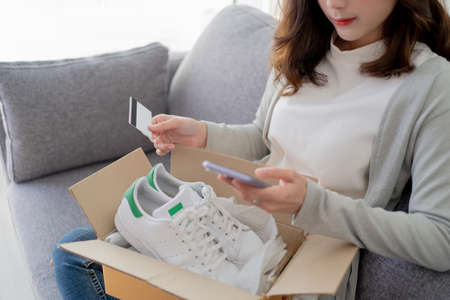 Young woman received a parcel box for shopping online by paying by credit card.