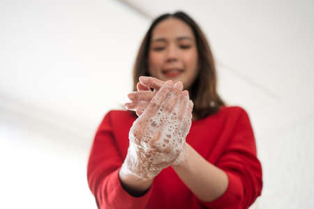 Asian woman are using soap to wash hands in the room to eliminate the COVIC-19 virus, close up of a woman's hand.