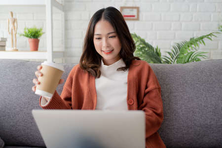 Smiling woman enjoying morning coffee and using a laptop to work. She sits on the sofa at home.
