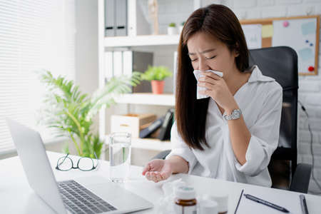 Young Asian women feel sick. She was taking medicine on the desk in the office.
