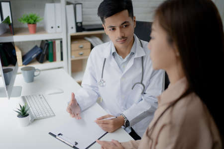 Doctor is explaining how to treat patients in the office. Imagens