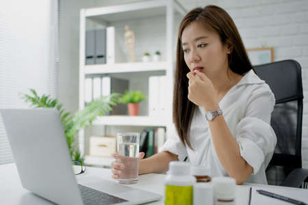 Asian business woman drinking water and taking medicine. She felt sick.