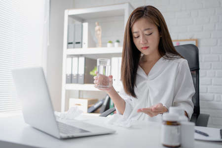 Young business woman taking medicine in the office
