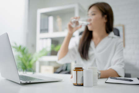 Business woman drink water. She felt sick. A close up of a medicine bottle on the desk.