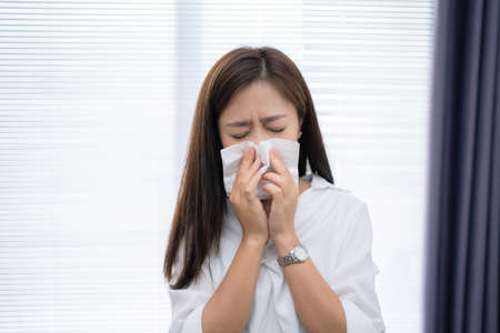 Asian woman sneezes at home. She uses a tissue to cover her mouth.