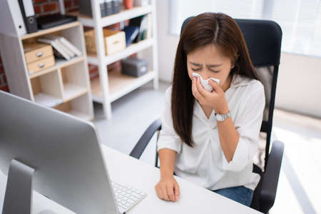 Asian woman sneeze. She is resting and working at home. Imagens