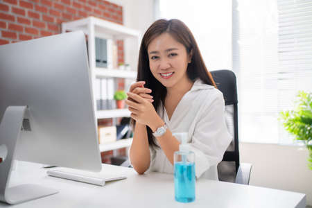 Asian woman use alcohol gel to wash hands, kill germs and viruses at the office.