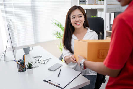 Businesswoman smiling while receiving boxes from home delivery service. She is in office. Imagens