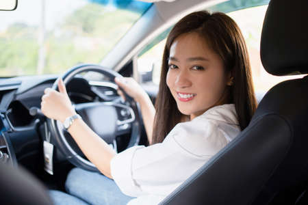 A smiling Asian woman driving to work, she is in the car.
