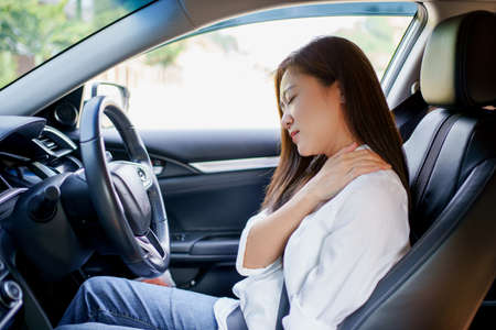 Asian business woman has shoulder and neck pain in the car. Imagens