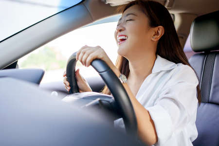Asian woman driving on vacation. She was smiling and happy. Imagens