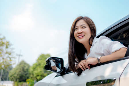 Beautiful Asian woman smiling and looking at the sky in a white car. Imagens