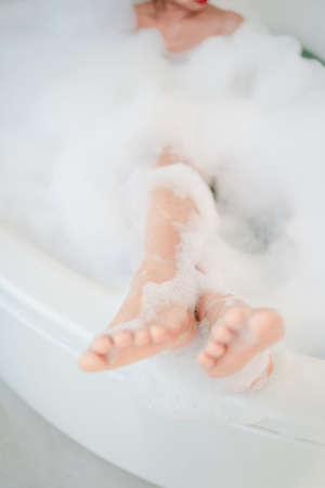 Woman's feet in the bath. She is taking a shower in the bathroom.