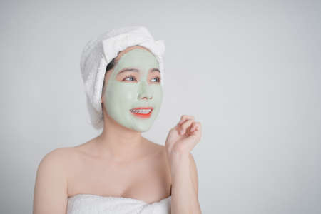 Asian woman is facial masks on white background with copy space.