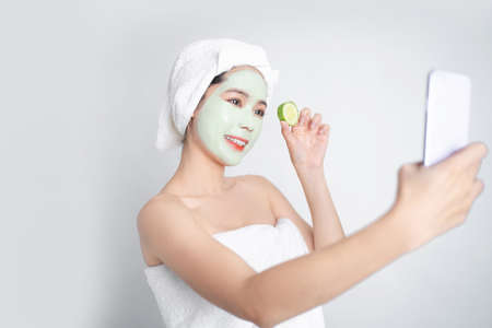 Young Asian woman smiling relaxedly with a facial mask. She is taking a picture with a smartphone.