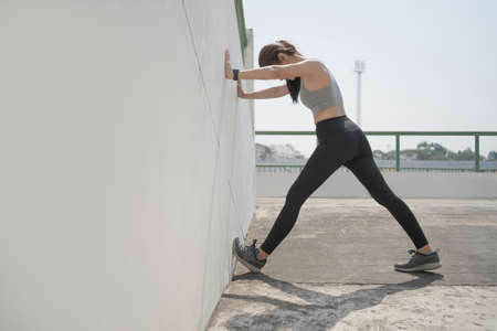 Woman in sportswear is warming up outdoors in the morning. Banco de Imagens