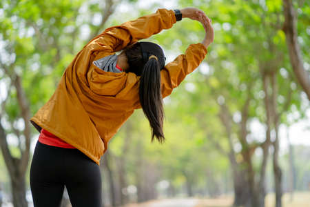Healthy young woman warming up outdoors. She is stretching her arms before training run.