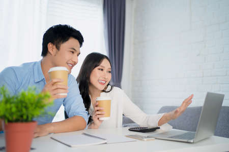 Young Asian couple uses a laptop to chat on an online website. They are happy to do business together at home.