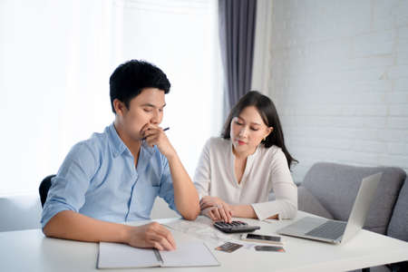 Young Asian couples are calculating their income. They are stressed Banco de Imagens