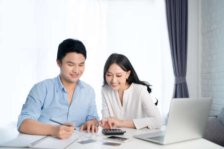 Asian couples are calculating their expenses with a calculator. They are happy. Banque d'images