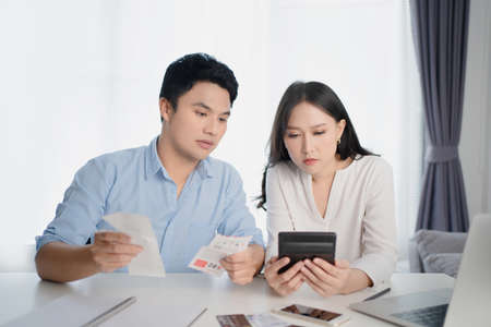 Young Asian couple is calculating their expenses with a home calculator. They feel stressed.