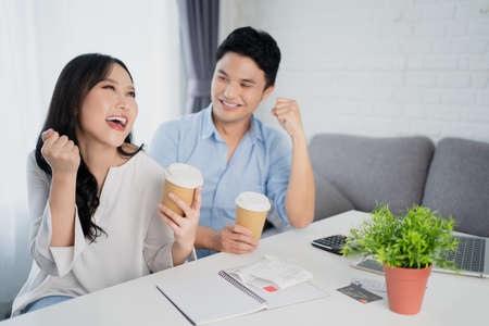 Young Asian couple doing business together at home with laptop. They are happy.
