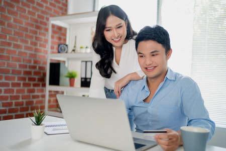 Young Asian couple is using a laptop while shopping at an online website at home. They are happy to enjoy the weekend. Banco de Imagens