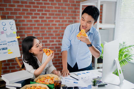 Young Asian colleague is eating pizza and exchanging ideas on his desk. They are happy in the office.