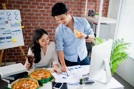 Young Asian colleague is eating pizza and sharing ideas on the desk in the office. Banco de Imagens