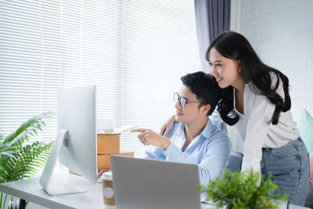 Young Asian couple startup family business. They work from home with the boxes of the online store preparing to deliver their products to their customers. Banco de Imagens