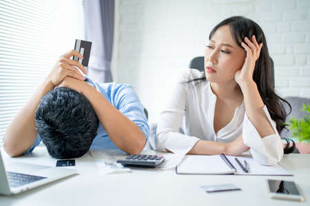 Young Asian couples are stressed. They have credit card financial problems from online shopping. Banco de Imagens