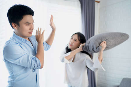 Asian couples quarrel at home. A man uses a hand forbidden to protect his girlfriend because he is unhappy with his actions.