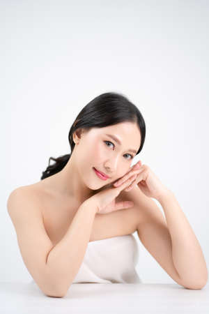 Asian beautiful women have a youthful face. She touched her white and bright skin. Isolated from the white background. Banco de Imagens