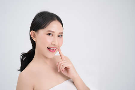 Youthful bright skin of a beautiful Asian woman is isolated from a white background. She was smiling and happy. Banco de Imagens