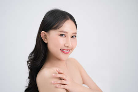 Youthful bright skin of a beautiful Asian woman is isolated from a white background. Banco de Imagens