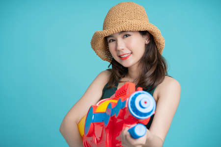 Beautiful Asian woman smiling and holding a plastic water gun for Songkran Festival in Thailand. On a blue background. Banco de Imagens - 165711268