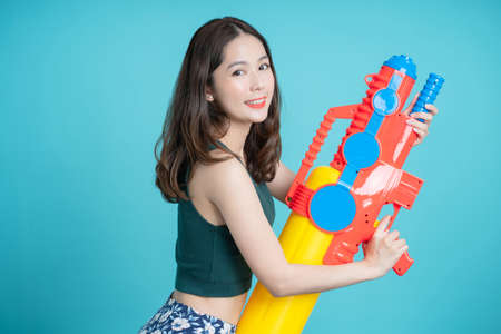 Smiling Asian woman stands sideways holding a water gun for Songkran festival isolated on a blue background.