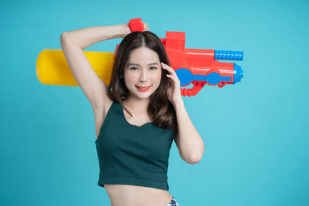 Beautiful Asian woman holding a plastic water gun at Songkran Festival, Thailand. Isolated on a blue background.
