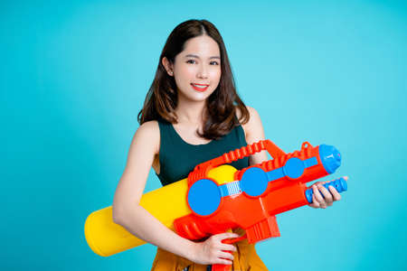 Asian women smiling and holding water guns for Songkran festivities in the studio. Isolated on a blue background.