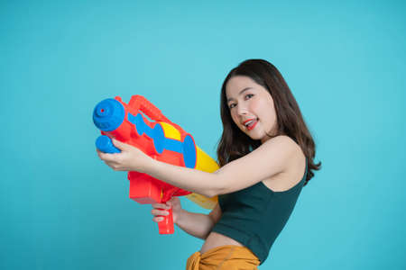 Asians use water guns for a songkran festival in a studio on a blue background. Banco de Imagens - 165711334