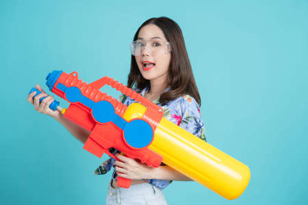 Beautiful Asian woman holding a plastic water gun and isolated on a blue background in the studio. She was ready for the Songkran Festival in Thailand.