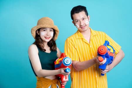 Asian couple holds a plastic water gun for a Songkran festival in Thailand. Isolated on a blue background in the studio.