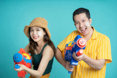 Asian couple holding plastic water guns happy for Songkran festival, isolated on blue background.