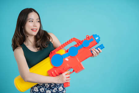 Asian woman smiling happily and holding a plastic water gun for Songkran Festival in Thailand. Isolated on a blue background in the studio