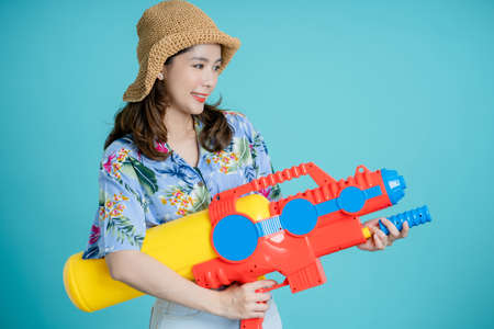 Beautiful Asian woman holding a plastic water gun for Songkran festivities in Thailand. Isolated on blue background in studio with copy space. Banco de Imagens - 165711170