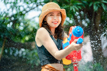 Asian beautiful woman splashed by water for Songkran Festival. She is using a water gun with a copy space.