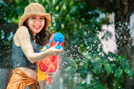 Asian woman splashed by water for Songkran festival. She uses a water gun.
