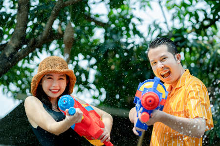 Asian people enjoy water guns playing in the Thai Songkran Festival in the summer of April. Banco de Imagens