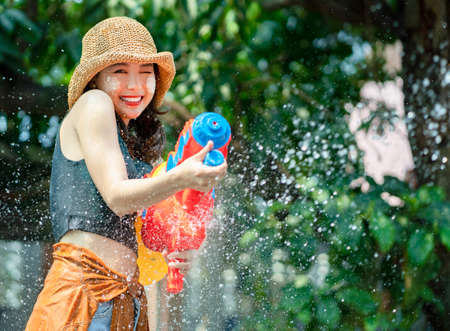 Smiling Asian woman was splashed by water. She is using a water gun for Songkran Festival. Banco de Imagens
