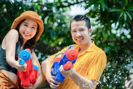 Asian people enjoy water guns playing during the Songkran Festival in the summer of April. They got splashed while playing in the water.